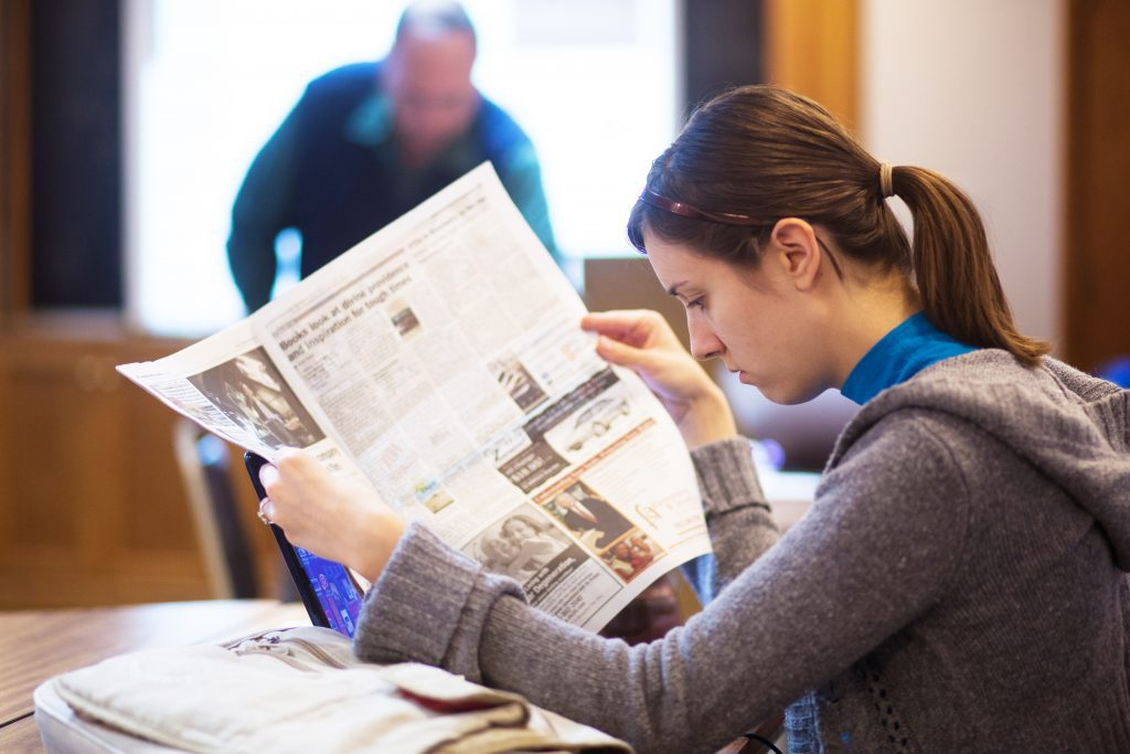 Journalism Major student in class looking at newspaper