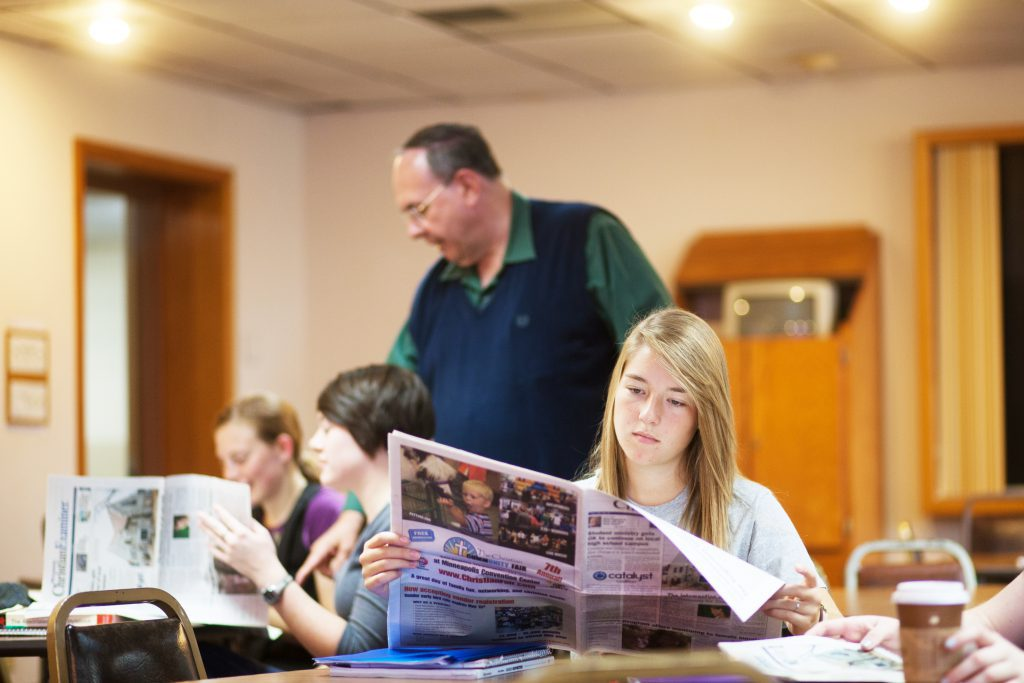 Students in class looking at newspapers