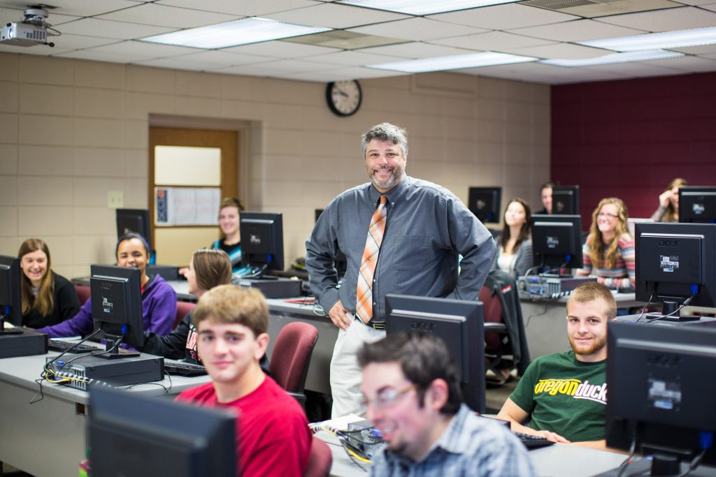 Information Systems Degree Professor and students in computer lab smiling