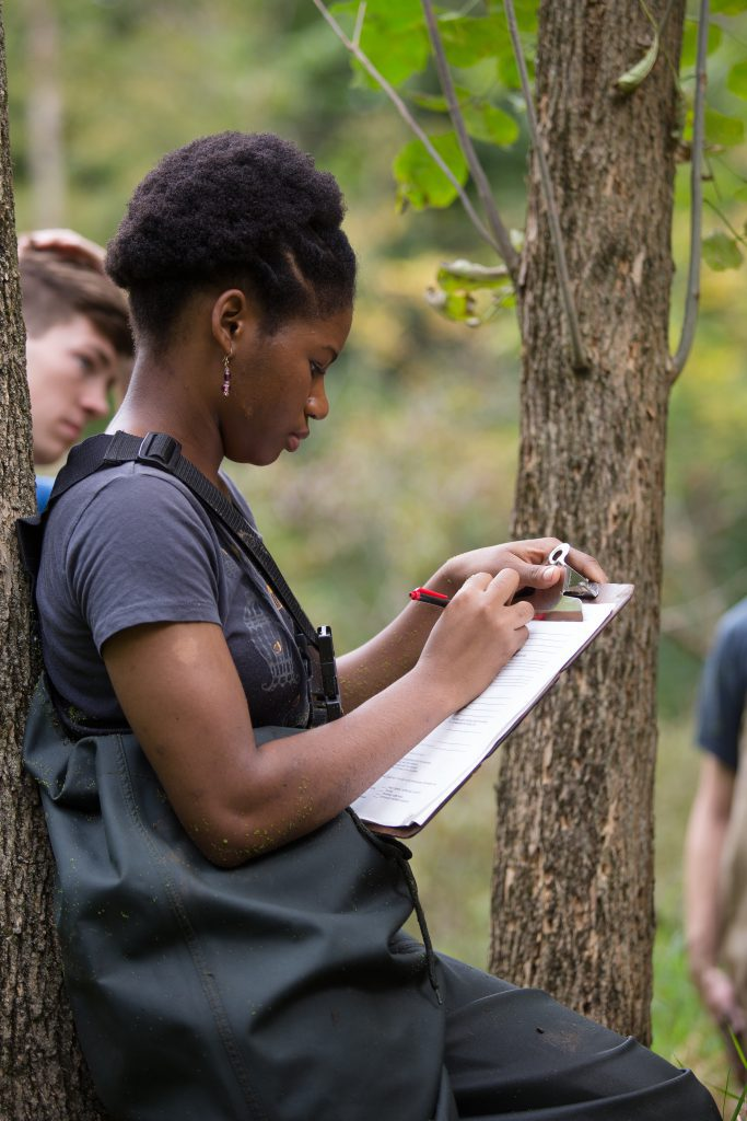 Environmental biology major student in ecology lab outdoors taking notes