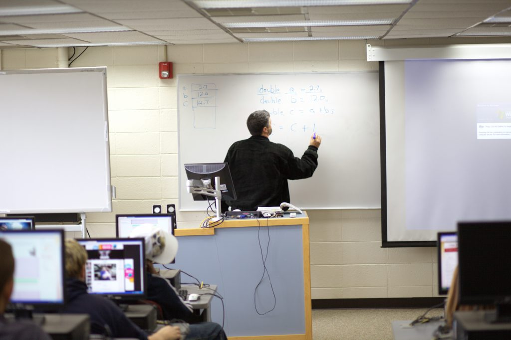 Professor in computer lab writing math on the whiteboard