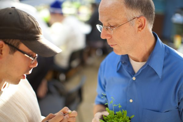 Professor and student observing plants