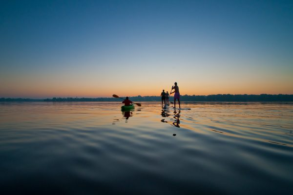 Students paddle boarding on the lake