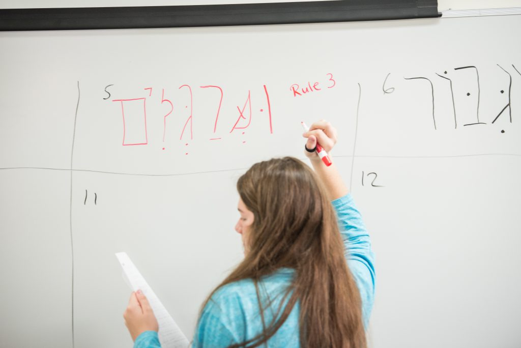 Student at whiteboard translating the bible
