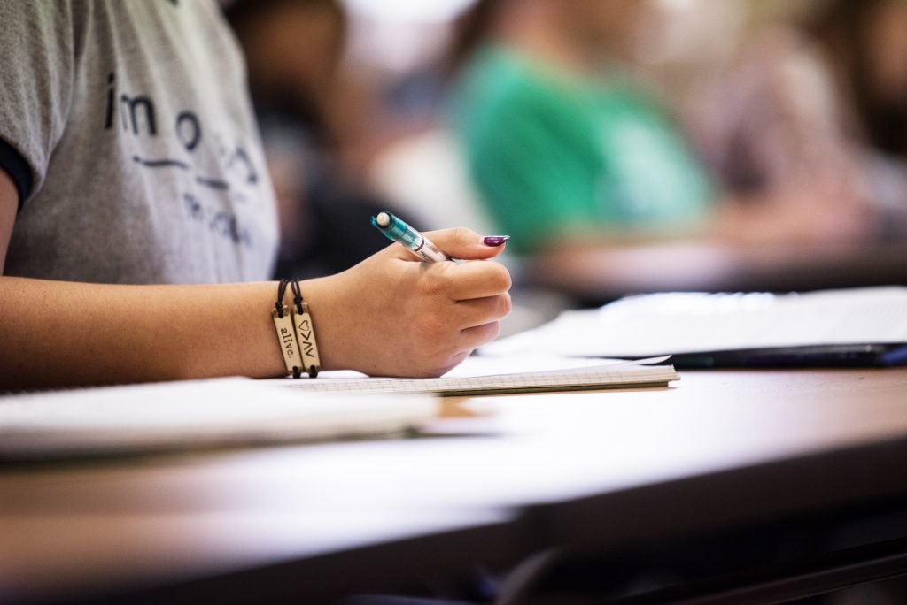 students hand taking notes in class