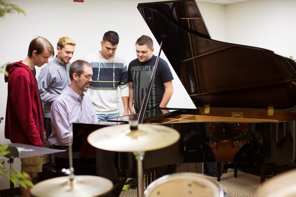 Professor playing the piano with students watching