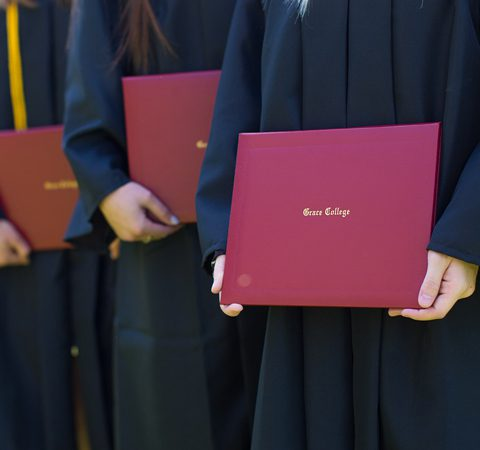 Grace College students holding their diplomas at graduation