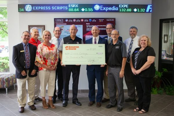 Business professors and Dr. Bill Katip presented with a check from 1st Source Bank