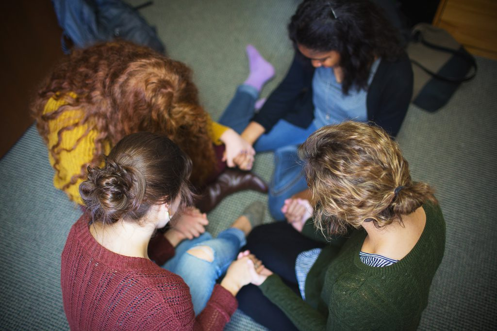 Students praying in a circle